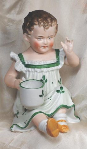 """GERMAN BISQUE PIANO BABY WITH CUP. 7"""" H. All-bi"""
