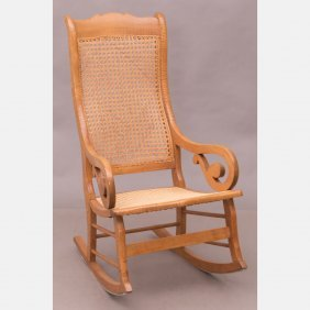 An American Walnut Rocking Chair With Caned Seat And
