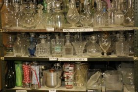 Shelf Of Small Clear Glass & Crystal Decanters Etc