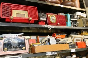 Two Shelves Of Alarm Clocks And Radios.