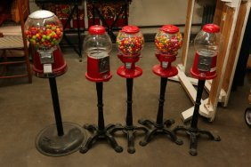 Five Gumball Machines On Stands.