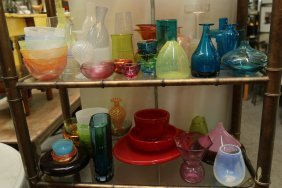 Two Shelves Of Assorted Colored Glass.