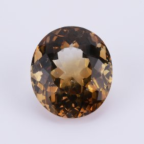 An Oval Brilliant Cut Orange Brown Topaz Cabochon With