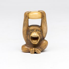 An Ivory Netsuke Of A Monkey Holding A Rock Above Its