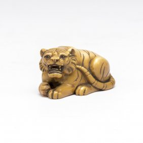 An Ivory Netsuke Of A Crouching Tiger With Onyx Eyes,