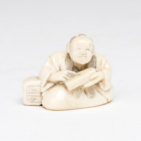 An Ivory Netsuke Of A Seated Man Holding A Box, Signed,