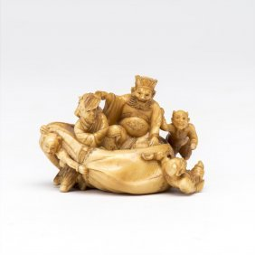 An Ivory Okimono Carving Of Deities In A Sack Dragged