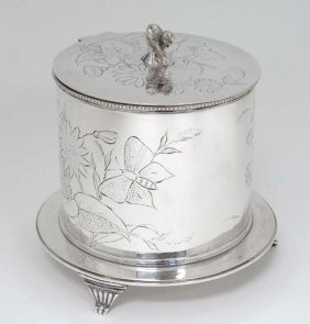 A Silver Plated Biscuit Barrel With Hinged Lid And