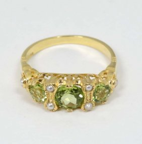 A Silver Gilt Ring Set With Three Graduated Peridot And