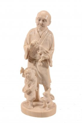 An Ivory Okimono Of A Man Holding A Rabbit