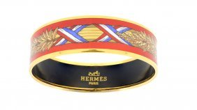 AN HERM�S RED ENAMEL AND GOLDTONE BANGLE BRACELET