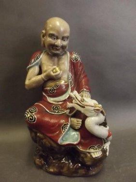 An Oriental Porcelain Figure Of Buddha Holding A Golden