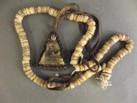 A String Of Tibetan Mala Beads, And A Metal Pendant In