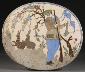 A  PERSIAN TIN GLAZED EARTHENWARE OVAL PLAQUE