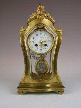 FRENCH MANTLE CLOCK IN A GOLD CASE WITH  BEVELED GL