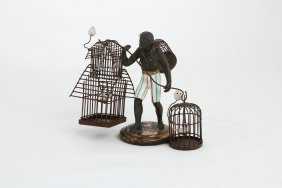 Black Man Holding Two Bird Cages, Each Cage Has One