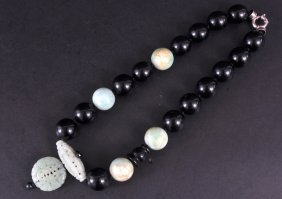 A HEAVY TWO COLOUR JADE NECKLACE AND PENDANT.